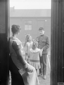 Two young Belgian girls greet their father outside their home on his return from work, as their mother looks on from the doorway. Birtley-Elisabethville, Co. Durham, 1918. IWM Q 27746