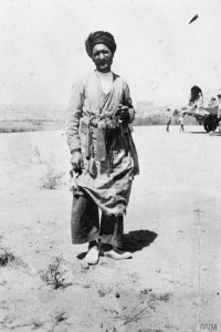 Persian man posing for a photograph. Note a truck with British troops in the background. The Service of the 9th Battalion, Royal Warwickshire Regiment in the Persian Campaign, 1918. IWM Q 73032